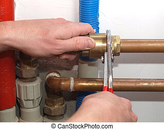 Fixing heating system - Worker hands fixing heating system...