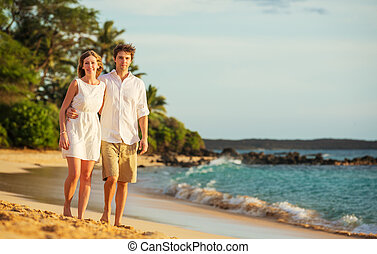Young couple in love walking on the beach at sunset - Young...