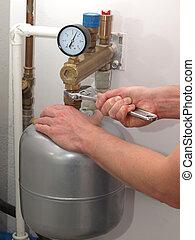 Pressure vessel repair - Plumber hands repairing pressure...