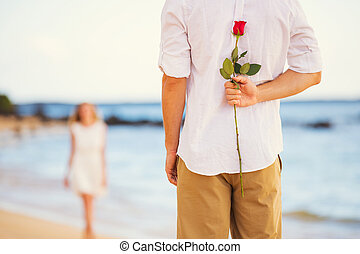 Young Couple in Love, Man holding surprise rose for...