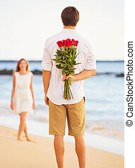 Young Couple in Love, Man holding surprise bouquet of roses...