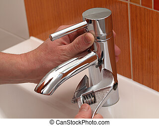 Plumber work - Plumber hands repair water tap with spanner