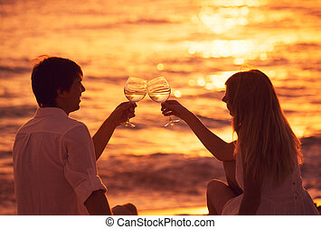Silhouette of couple enjoying glass of champagne on tropical...
