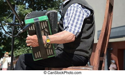 stage accordion outdoor - senior man playing with an old...