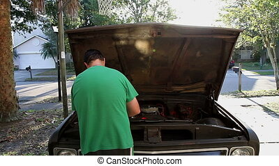 Adding coolant to classic truck - 30's man adding coolant to...