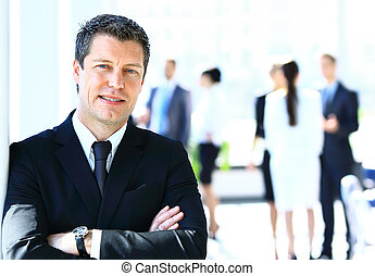 Happy businessman standing in front of his colleagues in...