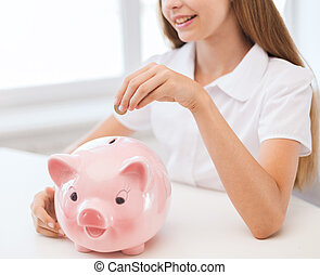 smiling child putting coin into big piggy bank - education,...