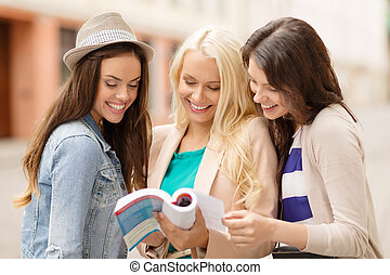 beautiful girls looking into tourist book in city - holidays...