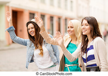 three beautiful girls waving hands - holidays and tourism...