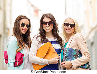 three smiling women with bags in the city