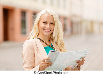 smiling girl with tourist map in the city - holidays and...