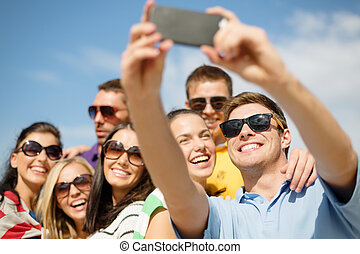 group of friends taking picture with smartphone - summer,...