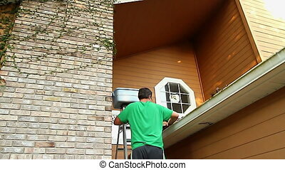 Man on Ladder Cleaning Gutters - 30s Man on Ladder Cleaning...