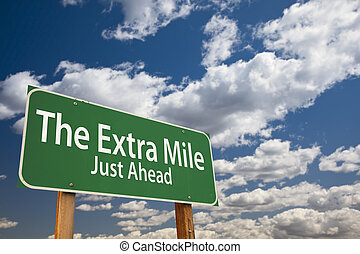 The Extra Mile Just Ahead Green Road Sign Over Sky - The...