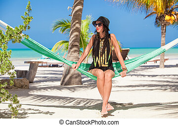 Young woman sitting in hammock on the beach