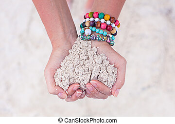 Close-up of sand heart in woman's hands decorated with...