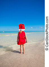 Back view of Little cute girl in red hat santa claus on the...