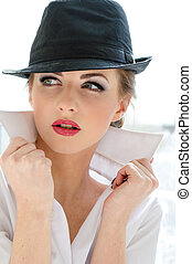 Headshot of young business woman wearing man's shirt and hat