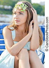 Young woman enjoying sunny day on sun lounge - Portrait of...