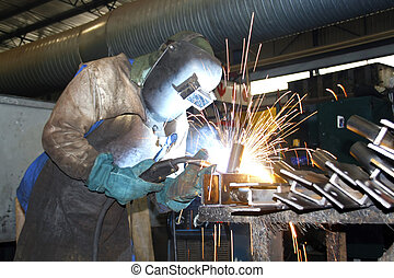 Artisan Welding - Artisan wearing protective gear while arc...
