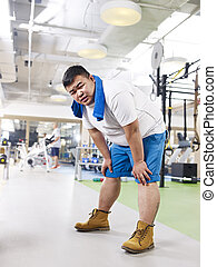 overweight man in gym - exhausted overweight young man in...