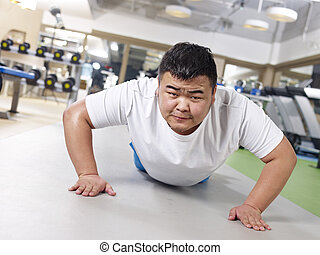 overweight man exercising - an overweight young man doing...