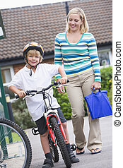 Mother and son outside school with bicycle
