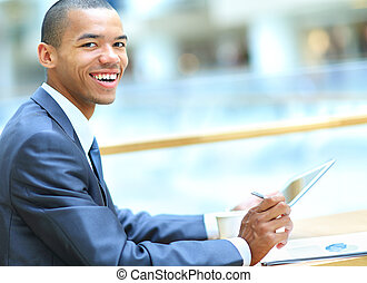 Handsome African American man with tablet computer in modern office