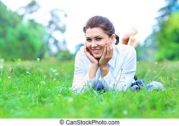 Portrait of a young professional woman laying down on green...