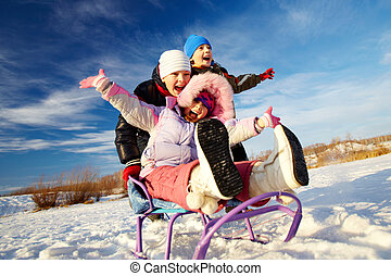 Riding on sledge - Friendly kids in winterwear riding on...