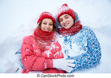 Couple in snow - Portrait of happy young couple lying on...
