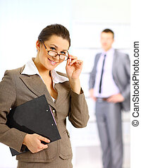 Successful business woman standing with her staff in background at office