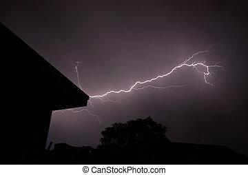 Lightening - A lightening strikes in a dark sky, around are...