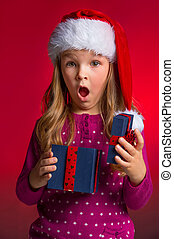 Surprised little girl with open gift box Standing over red...