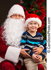 Little funny boy sitting on Santa Claus laps. Looking...