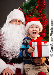 Little boy getting present from Santa Claus. Looking happy...
