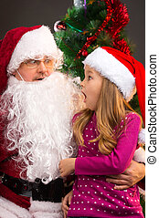 Surprised little girl looking at fake Santa Claus with fake...