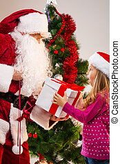 Little beautiful blond girl getting present from Santa Claus...