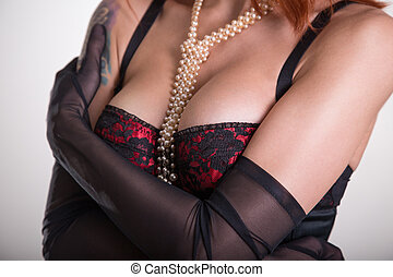 Close-up shot of a busty woman in vintage red bra, sheer...
