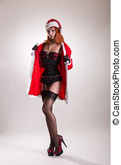 Pinup girl in Santa Claus suit and beautiful lingerie,...
