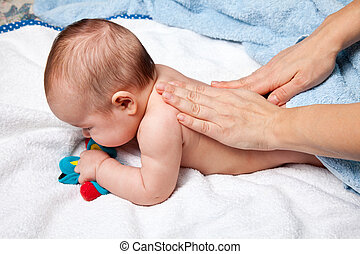 Baby back massage - Masseuse massaging 5 months infant