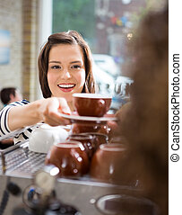 Customer Taking Coffee From Waitress In Cafe - Happy female...