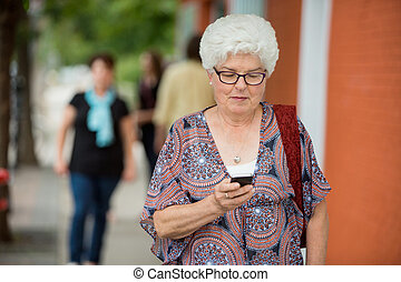 Senior Woman Messaging On Smartphone - Senior woman text...