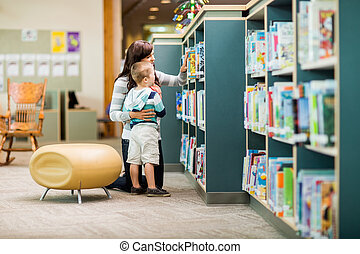 Teacher And Boy Selecting Book In Library