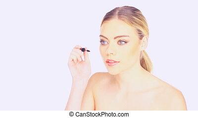 Beautiful woman applying mascara - Beautiful young woman...