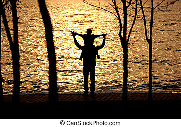 happy father and son wandering the sea coast - silhouette of...