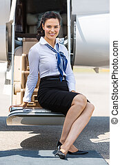 Airhostess Sitting On Ladder Of Private Jet - Full length...