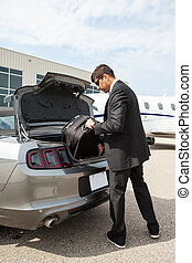 Businessman Unloading Luggage From Car At Airport Terminal