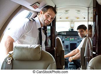 Pilot Entering Private Jet - Portrait of handsome pilot...