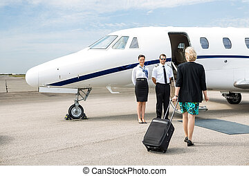 Businesswoman With Luggage Walking Towards Private Jet -...